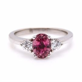 14K White Gold 1.34 CT Ruby and Diamond Ring: A 14K white gold ring featuring a 1.34 ct ruby with two round brilliant cut diamonds to each side above a pierced gallery.