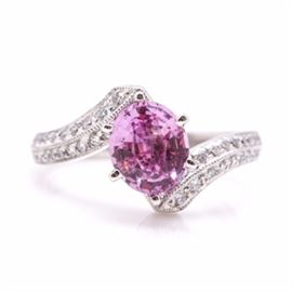 14K White Gold Pink Sapphire and Diamond Bypass Ring: A 14K white gold bypass ring showcasing an oval faceted pink sapphire flanked by two rows of round brilliant cut diamonds on each side.