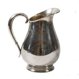 "International Silver Co. Sterling Silver ""Royal Danish"" Pitcher: A sterling silver pitcher by International Silver Co. in the Royal Danish pattern. The pitcher has a slanted top with spout, a graceful handle and a wide bottom and round base. The pitcher is unadorned except for some raised bands encircling the handle at the top and at the bottom. The underside is marked ""Royal Danish U.S.A. International Sterling 4 PTS 130 17"". Total approximate weight, 20.910 ozt."