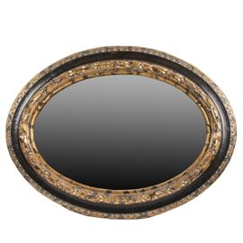 Black and Gold Mirror: A black and gold mirror. This wall hanging, oval mirror features an ornately decorated wooden frame in a distressed black and gold paint finish. A wire hanger is attached to the reverse. No maker's marks.