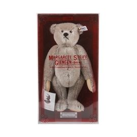 "Margarete Steiff Teddy Bear with Original Box: A reproduction vintage ""Teddybärr – Modell 1902"" Steiff teddy bear, designed by Richard Steiff, the nephew of the company founder Margarete Steiff. The bear is made of light gray-brown wool blend mohair, with tan felt paws, glass or plastic eyes, and an embroidered nose and mouth. The bear has a button and tag in its left ear, marked with number ""0150/32"", and it also comes with a sewn in fabric tag marked with the fabric content, and ""Made in Western-Germany"". A paper tag is attached to the bear's right paw, and it comes in the original box marked ""Margarete Steiff Giengen-Brenz""."