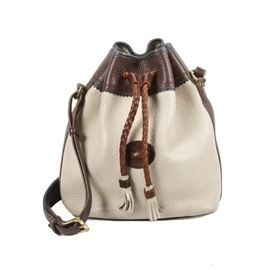 "Dooney & Bourke Leather Drawstring Handbag: A tan and white Dooney & Bourke leather drawstring handbag. The bag has a bucket style, with a leather drawstring top. The interior is lined in light colored suede, and it is labeled ""Dooney & Bourke, Inc. Made in U.S.A."" The serial number is A4852410."