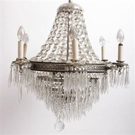 Austrian Crystal Chandelier: An Austrian crystal chandelier. Featured here is a large ceiling hanging chandelier with a wide silver tone filigree metal band around the center section. Attached to the center band are six candlestick style light sockets with hanging crystal prisms around their bases. The interior of the light has an additional three light sockets. The bottom portion of the light features tapered rows of metal rings adorned with hanging crystals. A spherical crystal ball dangles from the bottom. The top portion has a crystal chain canopy leading up to a scalloped crystal cap. Paperwork included with the chandelier indicates that it was originally hung in the Ogden Theater. No maker's marks.
