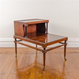 Vintage Mahogany Telephone Side Table: A vintage mahogany telephone side table. This table features a rectangular top with a raised second tier including a faux leather inlay rising on curved panels and rounded posts. The table rises on tapered legs joined by a perimeter stretcher and terminating on brass tone end caps and casters. There are no visible maker's marks.