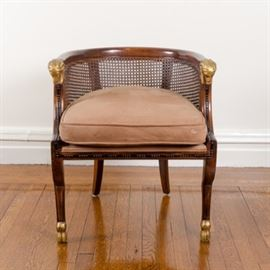 Regency Style Caned Armchair: A Regency style armchair. This armchair features a barrel back including a rounded edge over a cane inset panel with carved rams head hand holds. The chair includes a taupe tone cushion seat and it rests on curved legs ending in hoof feet. The rams head and hoof accents are painted in a gold tone.