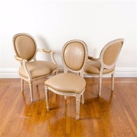 Set of Louis XVI Style Dining Chairs: A set of Louis XVI style dining chairs. These chairs feature a tan toned upholstered round back and rounded square seat that rises on fluted legs terminating in arrow feet. The set includes a pair of armchairs and a side chair.