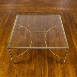 Glass and Metal Square Accent Low Table: A glass with metal low table. This vintage accent table features a square footprint with a beveled glass insert top over a brass and silver tone metal frame base. The base includes a beveled top and rests on metal spindle legs which end in arrow feet. There are two curved stretchers attached for additional support.