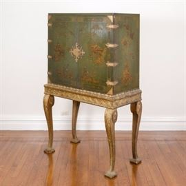 Vintage Asian Inspired Chest on Stand: An Asian inspired chest on stand. This rectangular top chest features two full length cabinet doors with green finish and gilt detail with gold tone hardware opening to two shelves. The chest sits on a gold tone frame with carved base rising on curved legs with carved acanthus leaf detail terminating on square feet. There are no visible maker's marks.