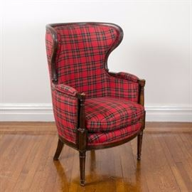 Plaid Upholstered Wingback Arm Chair: A plaid upholstered wingback arm chair. This chair features a wooden frame and curved crest rail leading to deep wings flanking an upholstered back and seat with padded armrests rising on turned wooden posts. The chair rests on a thin wooden apron and rises on tapered front legs terminating on ball feet. The chair is upholstered in a green and red plaid fabric. There are no visible maker's marks.