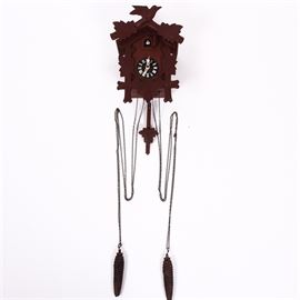 "Vintage German Black Forest Style Cuckoo Clock: A vintage German Black Forest style cuckoo clock. This clock features a wood frame with hand carved maple leaves and a bird perched at the top, right above a small hand painted cuckoo bird that emerges when the clock strikes the hour. Two pine cone weights and a leaf pendulum hang from the bottom. The clock face is marked ""Germany"" and the verso of the piece is stamped ""Made in Germany"". The pine cones are marked ""275 ET""."