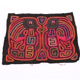 Hand Stitched Mola Panel: A hand stitched mola panel. Mola fabric is traditionally worn by the Kuna women of Panama. This piece depicts two abstract figures facing each other, created using layers of colorful fabric appliques with stitched embroidery throughout. The vibrant fabric pieces are woven into a black field.