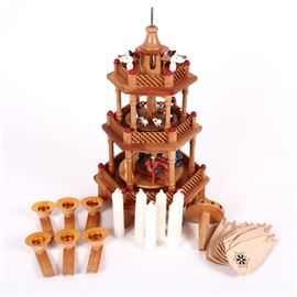 Traditional German Christmas Pyramid: A traditional German wooden Christmas pyramid. This windmill candle carousel features a revolving three-tier design and holds six candles. The heat from the candles propels the turbine on top of the pyramid, which rotates the three carousels with wooden figurines. Scenes portrayed are nativity, shepherds, and angels with hand-painted pieces. Exterior is natural finished and the item is unmarked.