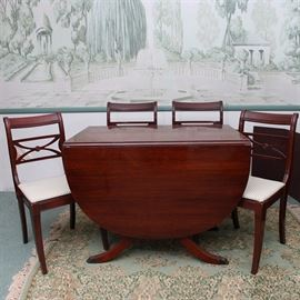 """Duncan Phyfe Style Dining Table and Chairs: A Duncan Phyfe-style drop-leaf dining table and four chairs with a mahogany finish. The rectangular table has two drop leaves, one of which has a rounded edge. It rests upon two pedestal bases with fluted, splayed legs terminating in bronze tone claw feet. The table comes with an additional 12"""" leaf and table pads. Each chair features a subtly scrolled back, an X-shaped splat, and sabre legs; two of the chairs have scrolled arms. Their seats are upholstered in cream fabric with a diamond pattern."""