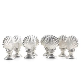 """Italian Silver Plate Shell Place Card Holders: A set of Italian silver plate place card holders. These eight holders feature scallop shell shaped top on round pedestal style bases with a beaded band. The underside of each is marked """"Made in Italy for Gump's""""."""