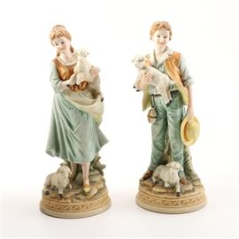 """Ethan Allen American Traditional Porcelain Bisque Figurines: A pair of Ethan Allen American Traditional porcelain bisque figurines. These figurines depict an 1800's era boy and girl in pastoral dress, holding lambs in their arms with one at their feet in a palette of light green, ivory, tan with yellow accents on round pedestals. Both are in a matte finish and are marked to the underside """"Ethan Allen American Traditional Interiors, 3211B."""""""