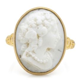10K Yellow Gold Cameo Ring: A 10K yellow gold cameo ring. This ring features an oval bezel set white glass molded cameo with milgrain detail. The shoulder of the ring has decorative detail.