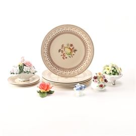 """Johnson Bros. Old Granite """"Fruit Sampler"""" Dishes With Floral Figures: A group of Old Granite Fruit Sampler dishes by Johnson Brothers with porcelain flower figures. There are eleven pieces in total with five larger plates, two saucers, and four floral pieces. The flowers are by Royal Albert, Radnor, and more. The dishes feature fruit and foliage details with rust-tone trim."""