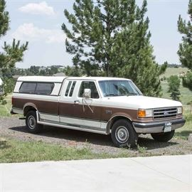 """1990 Ford F250 XLT Lariat Pickup Truck: A 1990 Ford F250 XLT Lariat 2-door pickup truck with a Leer """"Challenger"""" topper. At the time of cataloging the odometer reading was 119,172 miles. The VIN is 1FTHX25GXLKA40076. The 2-door truck is equipped with a V8 gasoline powered 7.5-liter engine, automatic transmission and rear wheel drive. The body is white with wide brown stripes on the sides and has Owens Classic XLR200 running boards along the sides. The truck is also equipped with air conditioning, and an AM/FM radio with a tape deck. The interior has tan carpet with tan cloth seats in front, and tan vinyl upholstery on the rear bench seat. Includes a trailer hitch and ball."""