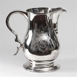 """Antique George III Sterling Silver Armorial Pitcher: A late 18th century Georgian sterling silver armorial pitcher. The pitcher features a pronounced spout and a curved handle that has a rest on the bottom. It has a rounded, bulbous bottom and slightly narrower top. It is supported by a round, flared base. The side is engraved, bearing the coat of arms of the Sackville lineage featuring a pair of leopards supporting a shield with a knight's Armor and crown above, with a ribbon marked in Latin, """"Aut Nunqua – Tentes Aut – Perfice"""". The underside features London hallmarks including an """"h"""" for the year 1783, a maker's mark """"IK"""", possibly for John King or John Kidder, a crowned leopard indicating London and a lion passant indicating sterling silver. Total approximate weight is 37.960 ozt."""