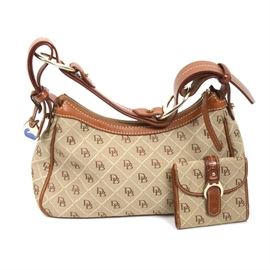 """Dooney & Bourke Handbag With Matching Wallet: A vintage Dooney & Bourke tan fabric and leather handbag with a matching wallet. The bag has a satchel style, with tan and brown logo fabric on the body, trimmed with tan leather. The bag comes with a matching wallet and both bag and wallet have gold tone hardware. The bags are both marked """"Made in China"""" and have a red, white and blue Dooney & Bourke sewn-in tag, plus serial number. The serial number for the bag is K057380."""