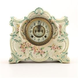 Ansonia Porcelain Mantel Clock: An Ansonia porcelain mantel clock. This ornate ceramic mantel clock features a scalloped top with scrolled sides, flowing floral accents and a molded flower accented base in a green hue. The clock face is white with black Arabic numbers and is framed in a textured brass frame with a removable brass back-plate to access mechanical works. The original key is included.