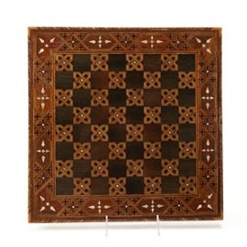 Wood Chess Board with Mother of Pearl Inlay: A wood chess board with mother of pearl inlay. The chess board has repeating geometric and linear designs including rhomboid shapes and variegated semi-gloss finished wood marquetry interspersed with patterns containing mother of pearl pieces. It is unmarked.