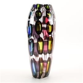 Scott Benefield Glass Vase: A glass vase signed by Scott Benefield. The piece is in an urn shape with a clear body. The body of the vase is decorated in black, blue, yellow, and red geometric patterns throughout. It is signed to the underside.
