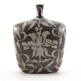 """Black and White Ceramic Bottle Vase: A black and white ceramic bottle vase. This black vase has a flattened shape with wide, angular shoulders and a thin neck, reminiscent of an old-fashioned bottle or flask; the surface is decorated with a silhouetted floral and foliate motif in white with small black dots throughout. A label on the underside reads """"Item# 294033 Made in Vietnam""""."""