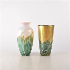 Hand Blown Art Glass Vases: A pair of hand blown art glass vases. The vases are gold and white tone opalescent glass with translucent green and gold paint ribbons curving up to the top. One piece has a tapered and flared edge, the other has a simple flared design throughout.