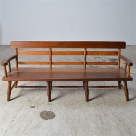 Deacon's Bench with Plank Seat: A deacon's bench of mixed woods. The bench features a thick plank seat with inwardly curving arms supported by turned stiles. There are eight canted legs with ring turned details connected by turned stretchers and the back has a wide top rail above two narrower horizontal slats supported by turned stiles.