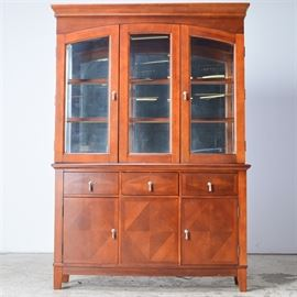 Cherry Finish China Cabinet: A cherry finish illuminated china cabinet. The upper portion has a mirrored back and glazed doors and sides. There are glass shelves and the interior is illuminated. The front has two doors with arched frames below a cornice. The lower section has a bowed front and features three drawers and two doors flanking a fixed panel. There is a fixed shelf in the interior of the storage area. The fronts of the drawers and doors have faux parquetry veneer and silver tone metal drop pulls.
