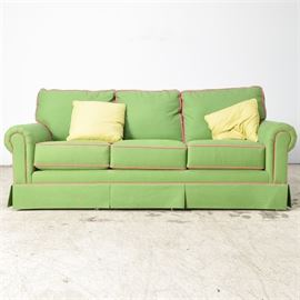 Green and Fuchsia Norwalk Upholstered Sofa: A green and fuchsia Norwalk upholstered sofa. The sofa has rolled Lawson style arms with six removable cushions for the seats and back. The sofa rests on six synthetic legs and includes two down throw pillows.