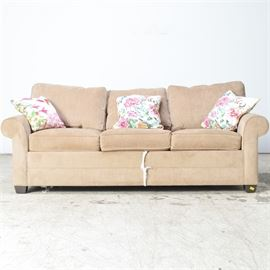 Tan Sleeper Sofa: A tan sleeper sofa. The sofa is constructed in the Lawson style with six removable cushions and rolled arms. The piece rests on six exposed wooden square feet and includes two down throw pillows.