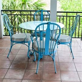 Cast Iron and Glass Round Patio Table and Four Chairs: A cast iron and glass round patio table and four chairs. This selection includes a turquoise-colored cast iron round patio table and four turquoise-colored cast iron armchairs with padded upholstered seats. The sets cast iron frame features scrolled accents throughout. Also included, a square-shaped glass table top.