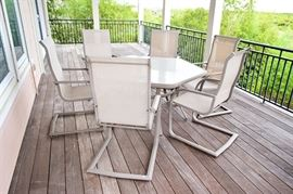 Outdoor Hexagon Table and Six Chairs: A outdoor hexagon table and six chairs. This table features a hexagon design with a gray metal frame and tempered glass top. Includes six chairs with gray metal frames, mesh seats. No makers mark is noted on this piece.