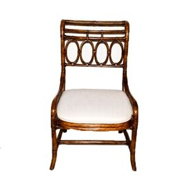 Rattan Side Chair: A rattan side chair. This chair features a curved back with rolled crest rail and a back panel with rounded details over an upholstered seat rising on splayed front legs joined by an H-stretcher. The seat is upholstered in an off white fabric. There are no visible maker's marks.