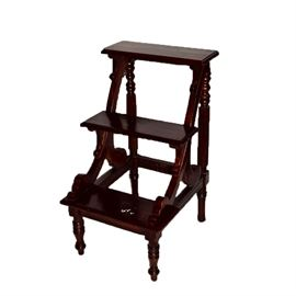 Wooden Library Steps: A set of mahogany-finished library steps. This item features three steps with scrolling supports. They stand on ring-turned legs.
