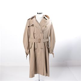 "Burberrys' Trench Coat: A Burberry trench coat. The coat comes with a detachable wool lining and an adjustable belt along the waist. It has a double breasted front closure with adjustable buckles along the sleeves. It is tagged to the interior ""Burberrys"" and monogrammed EJR."