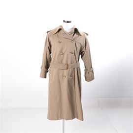 "Women's Burberrys Trench Coat with Detachable Wool Lining: A women's Burberry trench coat with detachable wool lining. This trench coat is beige, double breasted with eight front buttons, a matching belt, cuff fasteners, and a detachable wool lining that extends from the collar. It is marked ""Burberrys' of London"" on the inside tag."