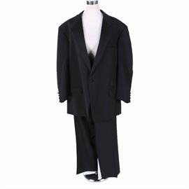 "Burberry Black Wool Tailored Tuxedo: A black wool tailored tuxedo from Burberry. This tuxedo includes a jacket with a single button front, hip pockets, and three button cuffs, and a pair of slacks with colorful suspenders, and a zipper and button front. There are several tags sewn in to the jacket, marked ""Fabric Loomed of Super 100's Wool"", ""Burberrys'"", and ""Louis Tanenbaum"". There is also a patch with the initials ""EJR"" in white stitching."