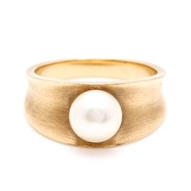 18K Yellow Gold Cultured Pearl Ring: An 18K yellow gold cultured pearl ring. This features a ring with a cultured pearl centerpiece resting in a valley between two raised borders.
