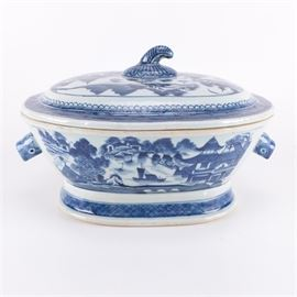Chinese Export Blue Boars Head Soup Tureen: A Chinese export blue soup tureen. Featured is a lidded ceramic soup tureen with a stem-shaped handle and a hogs head shape handle to each side. The piece depicts a blue and white river scene with traditional Chinese style boats and architecture.