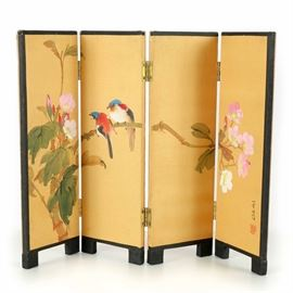 Watercolor and Gouache on Silk Room Divider: A watercolor and gouache on silk room divider. The divider has a wood frame with a black finish and features four brass tone hinged panels. Other features include four panels with images of blue, red and black parrots on a rhododendron bush with pink and white flowers and the divider stands on wood block feet. The image is signed by the artist on the first panel on the center edge.