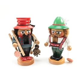 Wooden Nutcrackers: A pair of wooden nutcrackers. This pair of nutcrackers includes a figure with red hat, black hair and beard, ladder and pine cone accents and red shoes and a figure with green hat, tan hair and beard and colorful lederhosen. Both pieces stand on round wooden bases and have wooden levers on the back to operate the mouth mechanism. Pieces are marked.