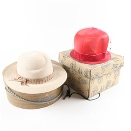Women's Hats and Boxes: A selection of women's hats and boxes. The selection features a woven white fedora style hat with a wide brim and a decorative brown band with a round hat box that displays a blue rope handle. The selection also features a red cloche style hat with a red band and red veil with decorative cloth accents. The hat features a square shaped box with a cloth tie and handle.