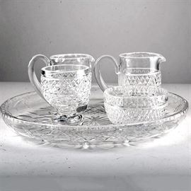 Assortment of Crystal Serving Pieces Including Waterford: An assortment of crystal serving pieces. This selection of crystal pies includes one creamer, one small bowl, one sugar cup and a round dish with diamond pattern. Pieces are marked to the undersides.