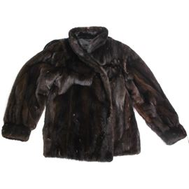 "Mink Coat by Mr. J: A mink coat designed by Mr. J. This piece is made from dark brown mink fur and features hook closures and two exterior side pockets. The black lining is embroidered ""Marcia D. Garvey on one side with a tag on the other side which reads ""Designed by Mr. J."""