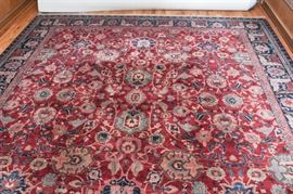 "Machine Knotted ""Esfahan"" Room Size Rug by Karastan: A machine knotted Esfahan room size rug by Karastan. This American made wool rug comes from Karastan's Samovar Teawash collection, and it features a rectangular field populated by floral designs in shades of indigo, light blue, green, and pink on a red ground. The field is surrounded by a compound leaf border, and the far ends have beige fringe. The rug is tagged underneath."
