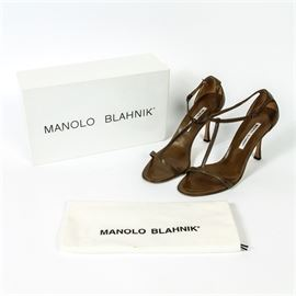 Manolo Blahnik Brown Leather Sandals: A pair of Manolo Blahnik T-strap sandals in size 39.5. This high-end style features a brown leather strappy upper with an adjustable ankle strap, a matching insole with a brand label at the heel and a spool style heel. The shoes are presented in the box with a Manolo Blahnik dust bag.