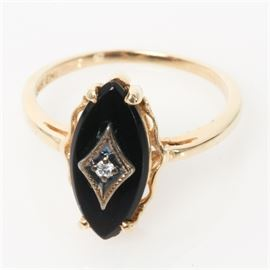 Vintage 14K Yellow Gold, Diamond, and Onyx Ring: A vintage 14K yellow gold ring featuring one round brilliant cut diamond mounted in a diamond shape against a flat marquise cut onyx stone.